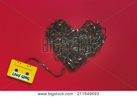 Audio Cassette Tape With The Inscription Love Song On A Red Background. Retro Technology Romance Concept