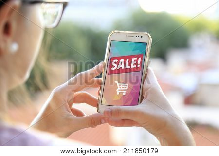 Girl holding a smartphone a sale advertising on the screen. Marketing, discount, internet, cell phone publicity.