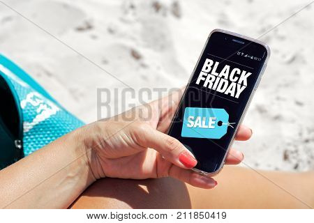 Woman on the beach with a cell phone in her hands. You can see a Black Friday advertising on the screen. Marketing, ecommerce, cell phone publicity.