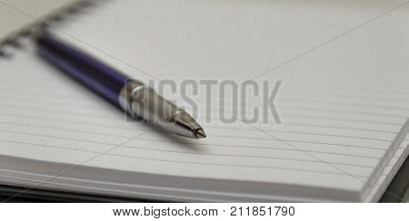 A silver and blue ball point pen on a notepad with a shallow depth of field