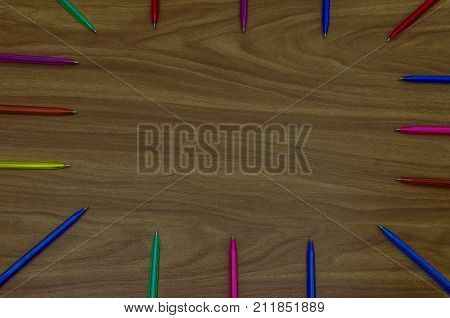Colourful pens arranged around the edge of a desk pointing inwards to an area of blank copy space