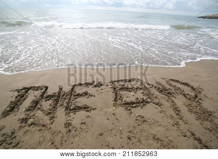 Word The End Written On The Sand And The Wave That Is Deleting T