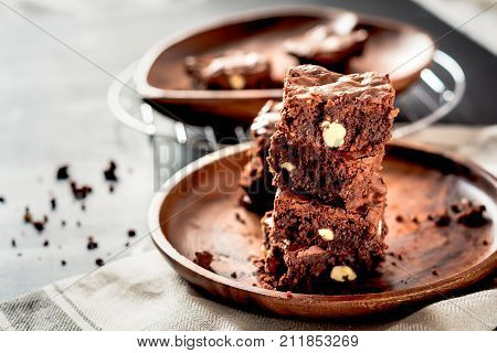 Piece of stack homemade dark chocolate brownies topping with almond slices and mint on wood table with copy space.