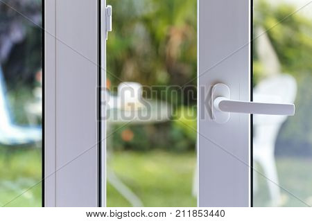 Open door of a family home. Close-up of the lock on the sliding door with the yard of background. White PVC door and double glass.