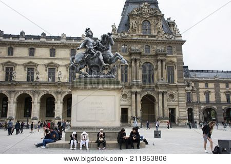 French People And Foreigner Travelers Sitting And Take Photo With King Louis Xiv Statue At Cour Napo