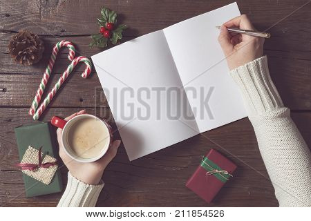 Top view of female hands holding a cup of coffee and writing a letter to Santa. Christmas presents and decorations placed on wooden table next to the letter