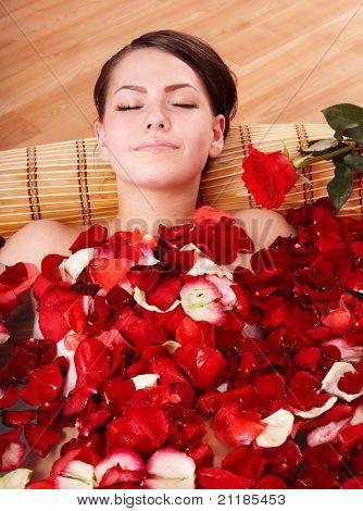 Beautiful young woman in rose petal swim water. Beauty spa.