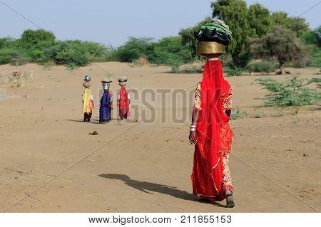 Indian ethnic women carries jar on her head and going for the water in well on the desert. Rajasthan India. Thar desert near Jaisamler