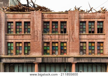 Front facade with stained glass windows of old brick building in downtown Portland Oregon being demolished