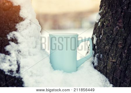 Blue Cup Of Tea Stands In Snow On The Tree Branches