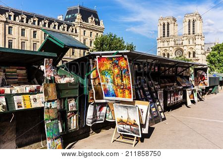 Paris France - June 23 2017: Vintage books and paintings in open bookmarket on embankment of River Seine near Notre Dame de Paris Cathedral.