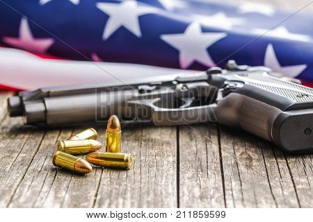 Pistol bullets, handgun and USA flag on old wooden table.