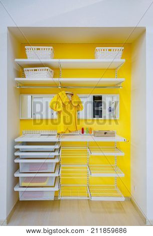 bright yellow walk -in closet with clothes and shelf, bin, box at home.