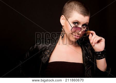Fashion hard rock bald woman in gold glasses and leather coat posing on black background