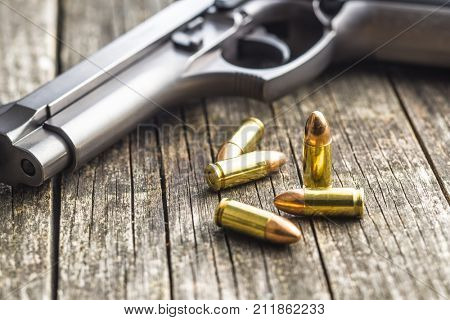 9mm pistol bullets and handgun on old wooden table.