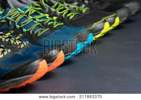 Four pairs of fitness trainers / running shoes lined up in a row on a gym floor with text / writing space