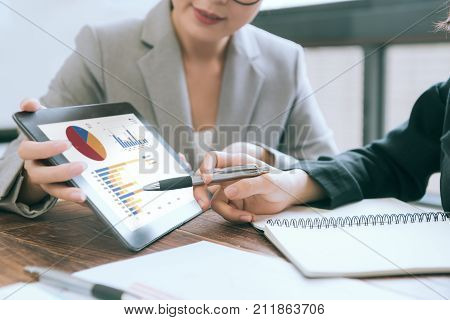 closeup photo of professional business people having meeting to discuss planning and pointing graph image on mobile digital tablet computer.