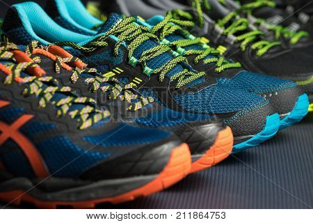 Three pairs of fitness trainers / running shoes lined up in a row on a gym floor