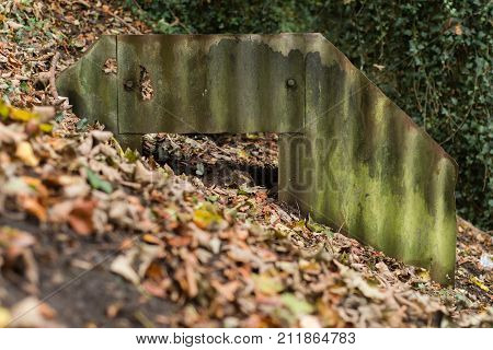 Ruined Anderson shelter rusted and partially buried, front. World War Two bomb shelter showing exposed corrugated iron sheets and steel plates