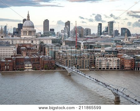 An elevated view of St. Paul's cathedral and The Millenium Bridge crossing the River Thames on a grey overcast day.