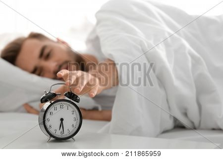 Young man switching off alarm clock signal while lying in bed at home