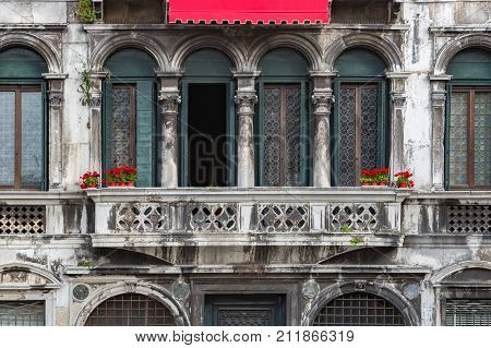 Venetian architecture. An ancient building in the Venetian style of architecture. Red flowers in red pots against the background of vintage building in Venice Italy. Ancient balcony in Venice Italy.