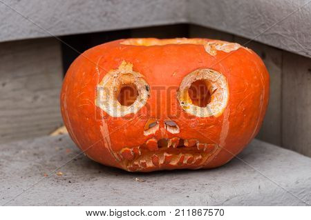 Orange carved out halloween pumpkin on stair step