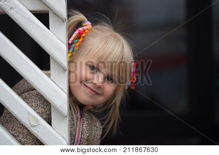 Portrait Of Little Cute Caucasian Kid Girl In A Jacket And  Colorful Scrunchy In A Hairtail Peeking