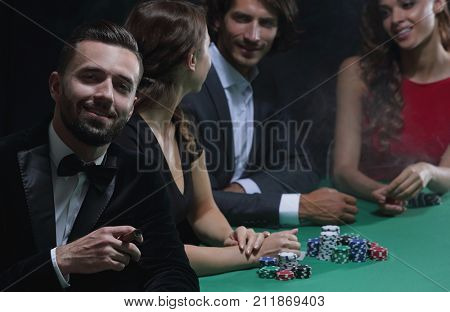 Man with cigar looking up from poker game in casino