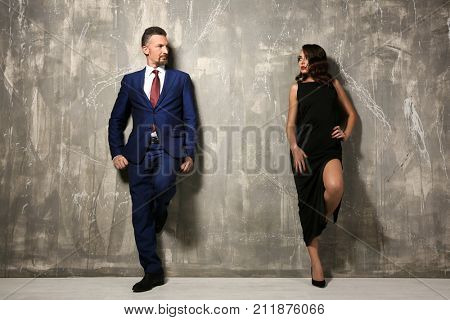 Attractive couple in formal wear near grey wall