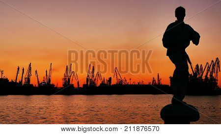 martial artist training alone on the sea pier, practising his moves on sunset and port cranes background. See my portfolio for more options.
