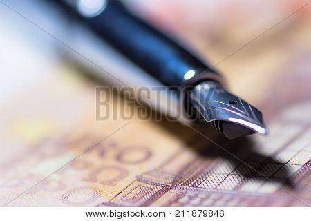Journalists bribery concept with pen and banknote.
