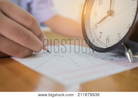 Students taking exams writing on optical form of standardized exam near Alarm clock with holding yellow pen for final examination in secondary school college university classroom Education concept