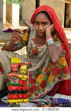 BHUJ RAN OF KUCH INDIA - 14 JANUARY 2015: The tribal woman in the traditional dress selling souvenirs for tourists in the ethnic village on the desert in of Ran of Kuch in the Gujarat state in India Ran of Kuch