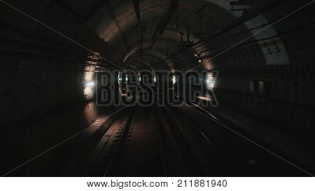 View of subway tunnel as seen from reverse of moving backward train. Fast underground train riding in tunnel of modern city. Underground train in Barcelona following its route