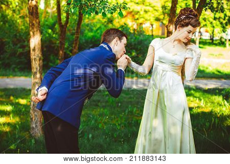Gentleman. Man kisses a hand to lady.