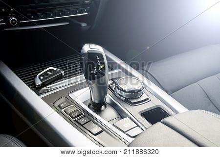 Automatic gear stick of a modern car and wireless car key car interior details. Soft lighting