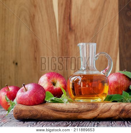 jug with apple cider vinegar and ripe red apples on a wooden table, selective focus