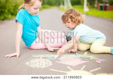 Little girls sisters chalking at the asphalt. Friendship childhood elder sister. Best friends children. Drawing with color chalk. Kids in kindergarten. Preschooler leisure time. Artistic talented kids. Children's drawings.