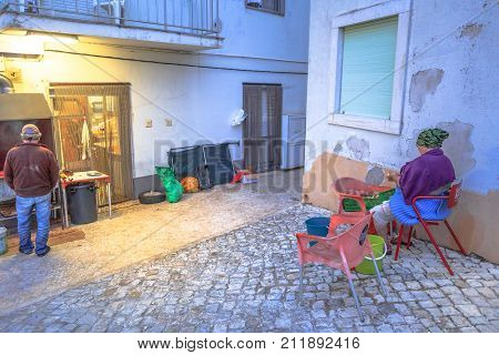 Nazare, Portugal - August 14, 2017: senior man cooks grilled sardines in back of a local restaurant while at Mulheres de Nazare, a typical woman of Nazare village, peals potatoes. Urban rural scene.
