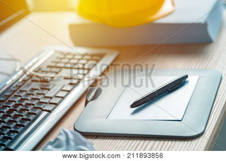 Graphic tablet and pencil on office desk in architecture and interior design project studio