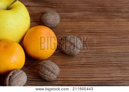 Fresh ripe mandarin, apple, walnuts on a wooden table. Organic sources of vitamins and minerals. Healthy nutrition. Brown wooden background with copy space for text
