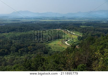 Dora Observatory DMZ Korea - September 8 2017: View to North Korea Propaganda village or Peace Village at Korean Demilitarized Zone with pole and flag of North Korea and fence in the front