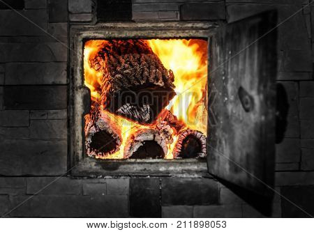 Open firebox inside the wall with burning firewood