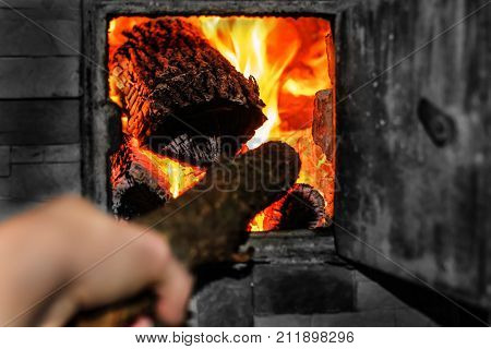 Open firebox with burning firewood. A man's hand is laying wood inside the furnace