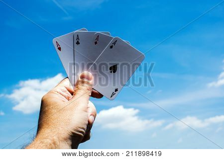 Poker cards on blue sky backgrounds.Four aces in hand