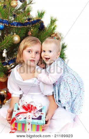 baby girl hugging her sister under the christmas tre
