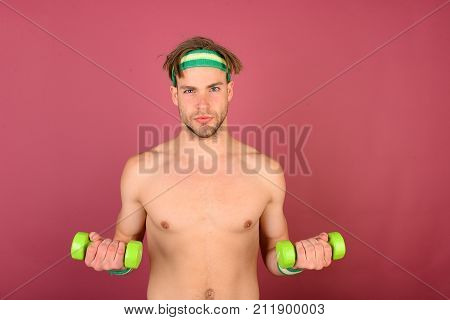 Man With Naked Torso Holds Green Dumbbells On Pink Background