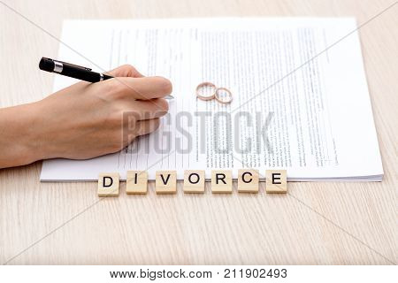 Concept Of Divorce. Word - Divorce with rings in the foreground a young woman in a plaid shirt signed divorce settlement in the background.