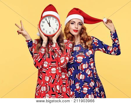 New Year. Young Woman in Christmas Santa hat with Clock Having Fun. Fashion. Pretty Playful Sisters Friends Happy Smiling in Stylish fashion Red Xmas Holiday Dress on Yellow. Christmas Colorful